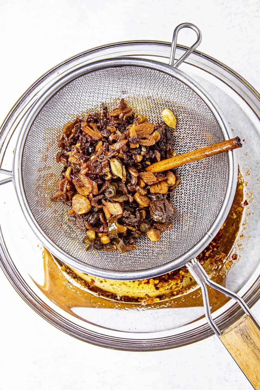 Straining the crisped bits of homemade chili crisp