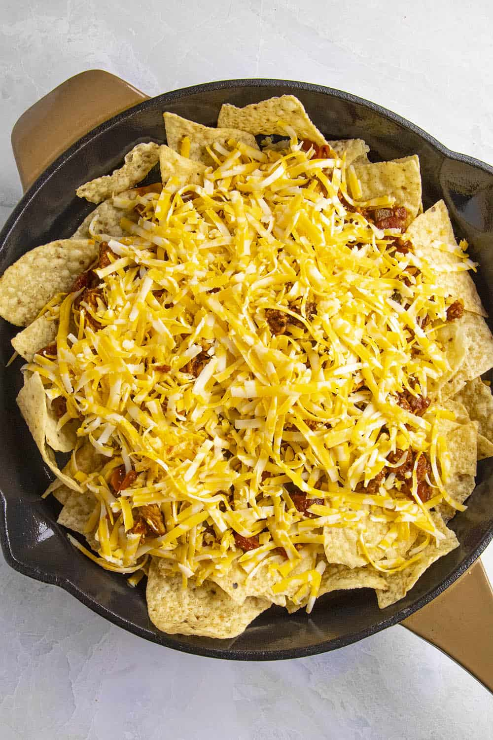 Add the shredded cheese over the Chipotle Chicken Nachos