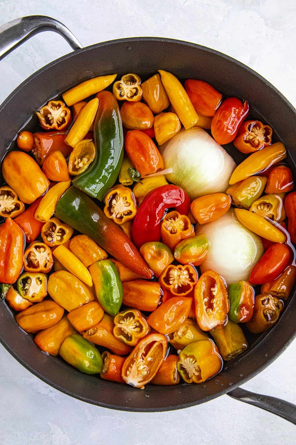 Boiling peppers and onions to make chili sauce