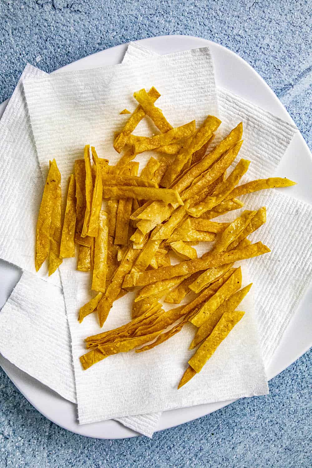 Crispy homemade fried tortilla strips draining on a plate