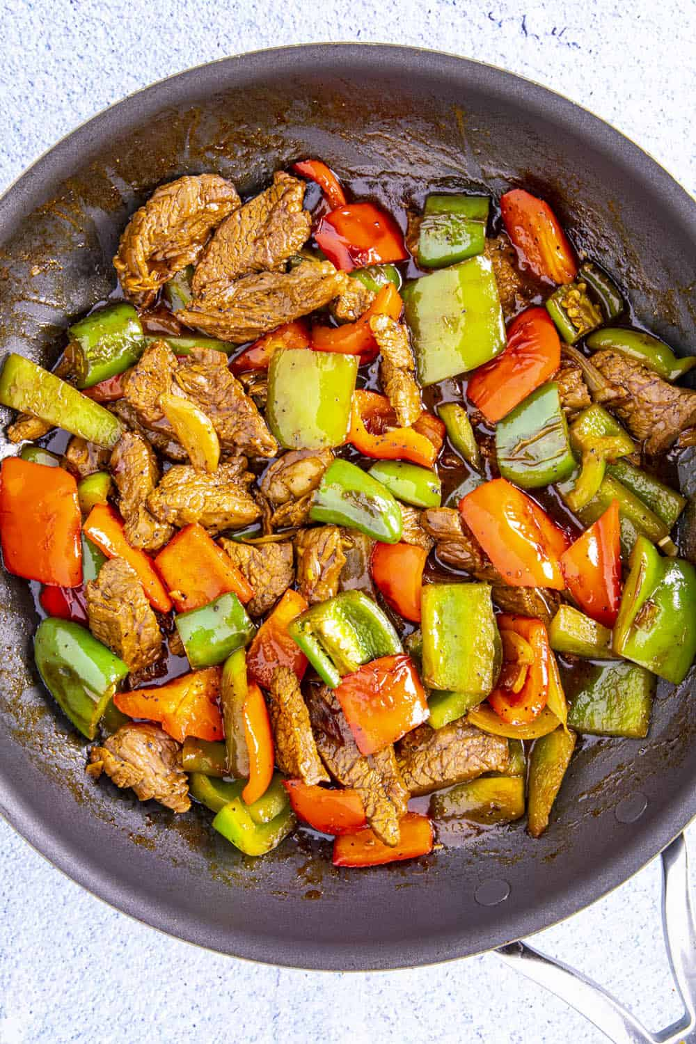 Combining the steak with peppers and sauce in a hot pan