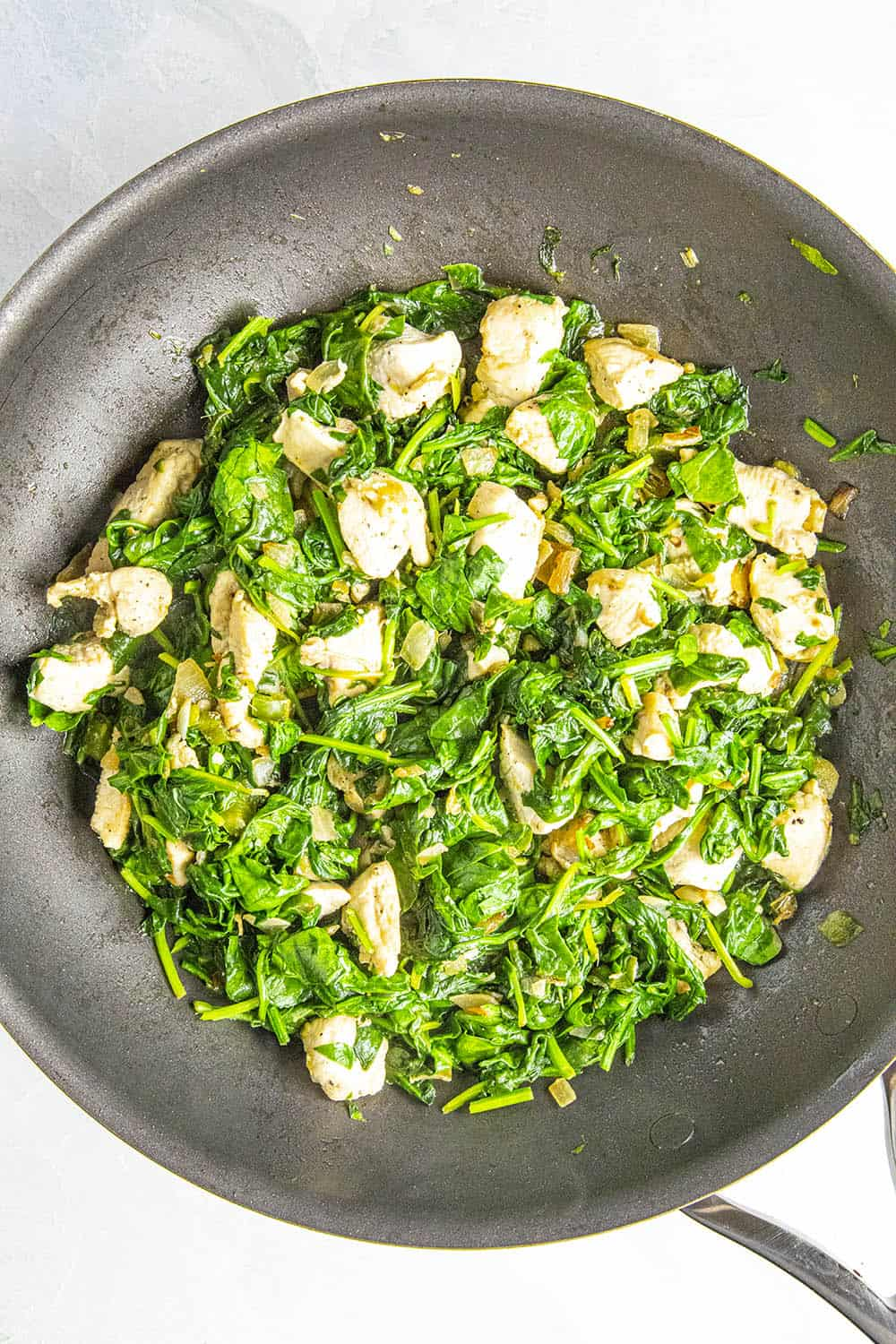Adding spinach to the pan for chicken saag