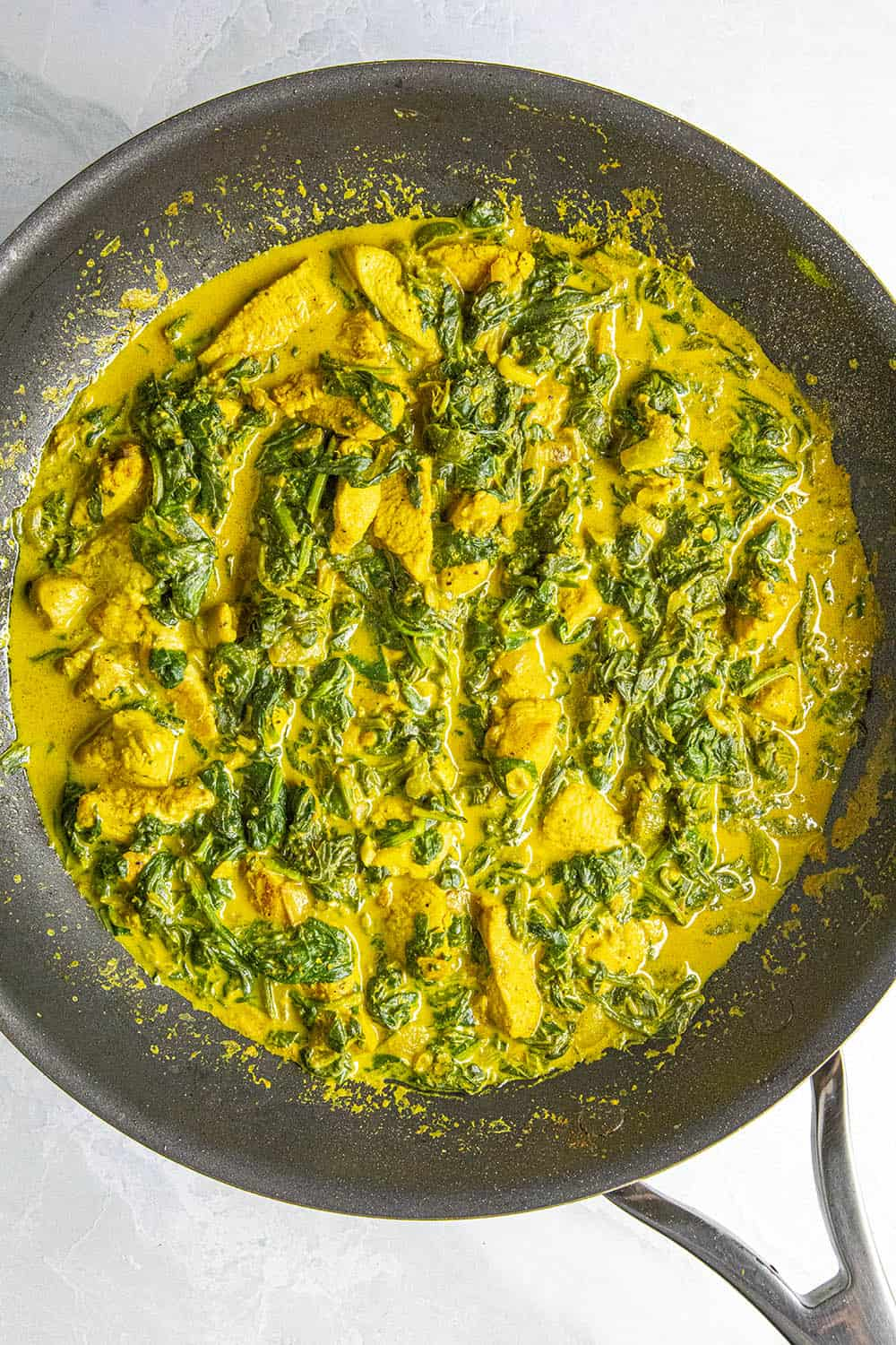 Simmering the chicken saag in a pan