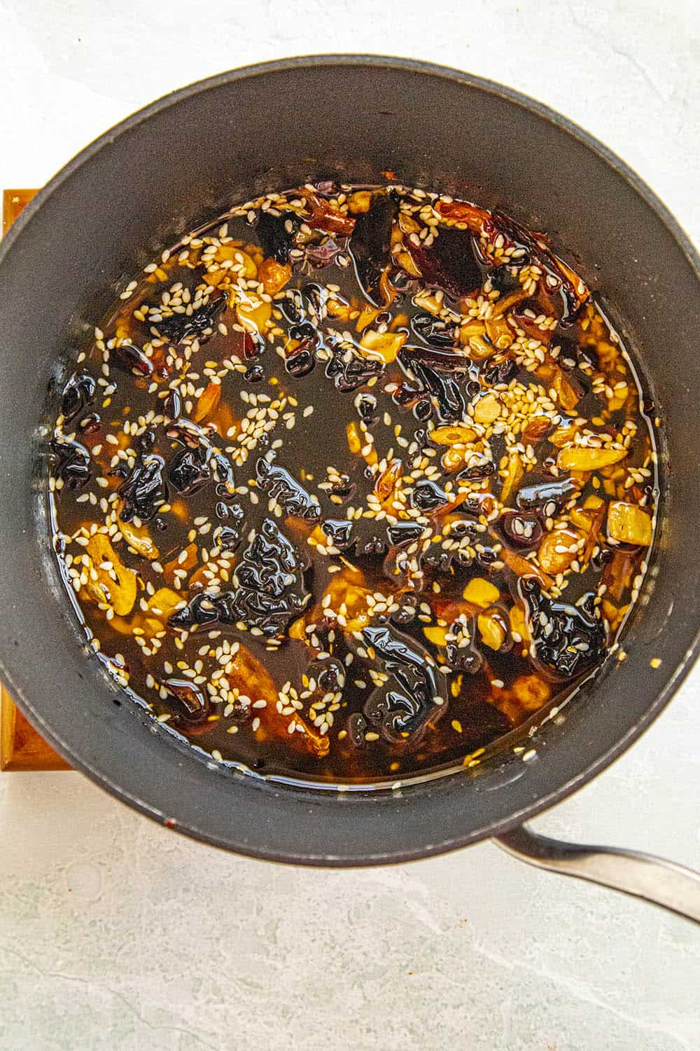 Cooking down the chili peppers in the hot oil with the sesame seeds, nuts and garlic