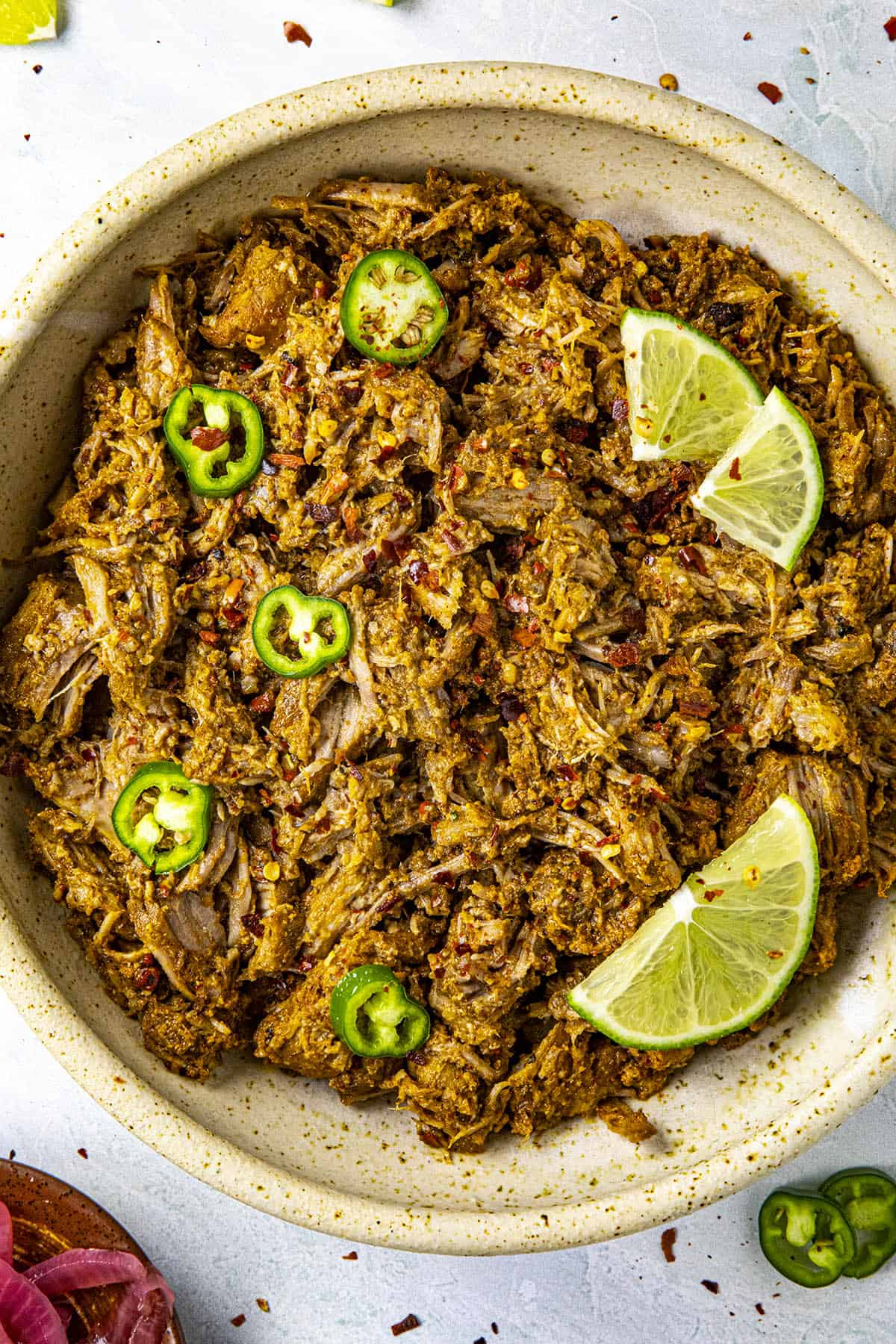 Shredded Cochinita Pibil in a bowl with lime wedges and sliced peppers