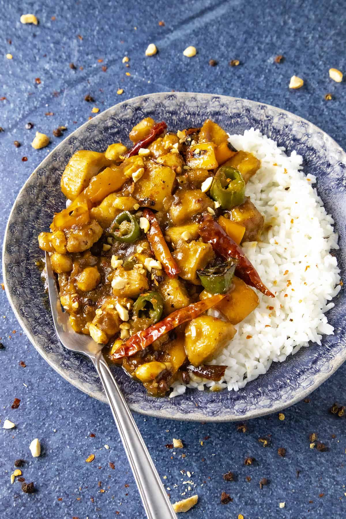 Szechuan Chicken on a plate with a fork, ready to serve