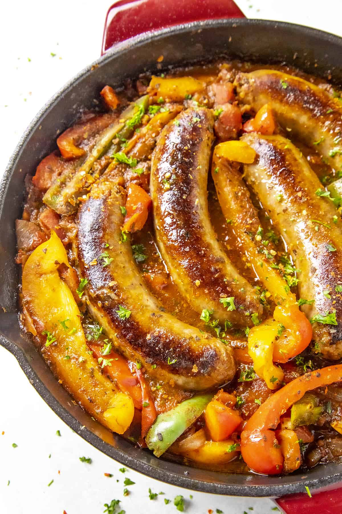 Sausage and Peppers in a hot pan with chili flakes and chopped green herbs