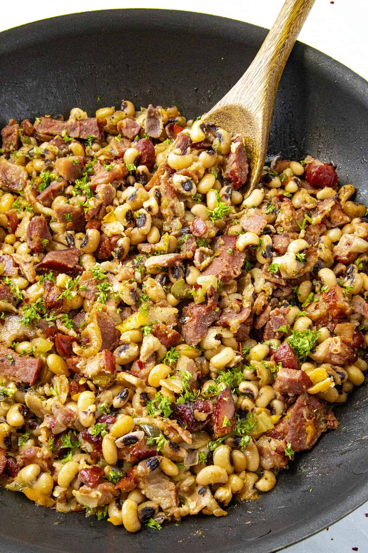 Taking a scoop of Black Eyed Peas from the pan
