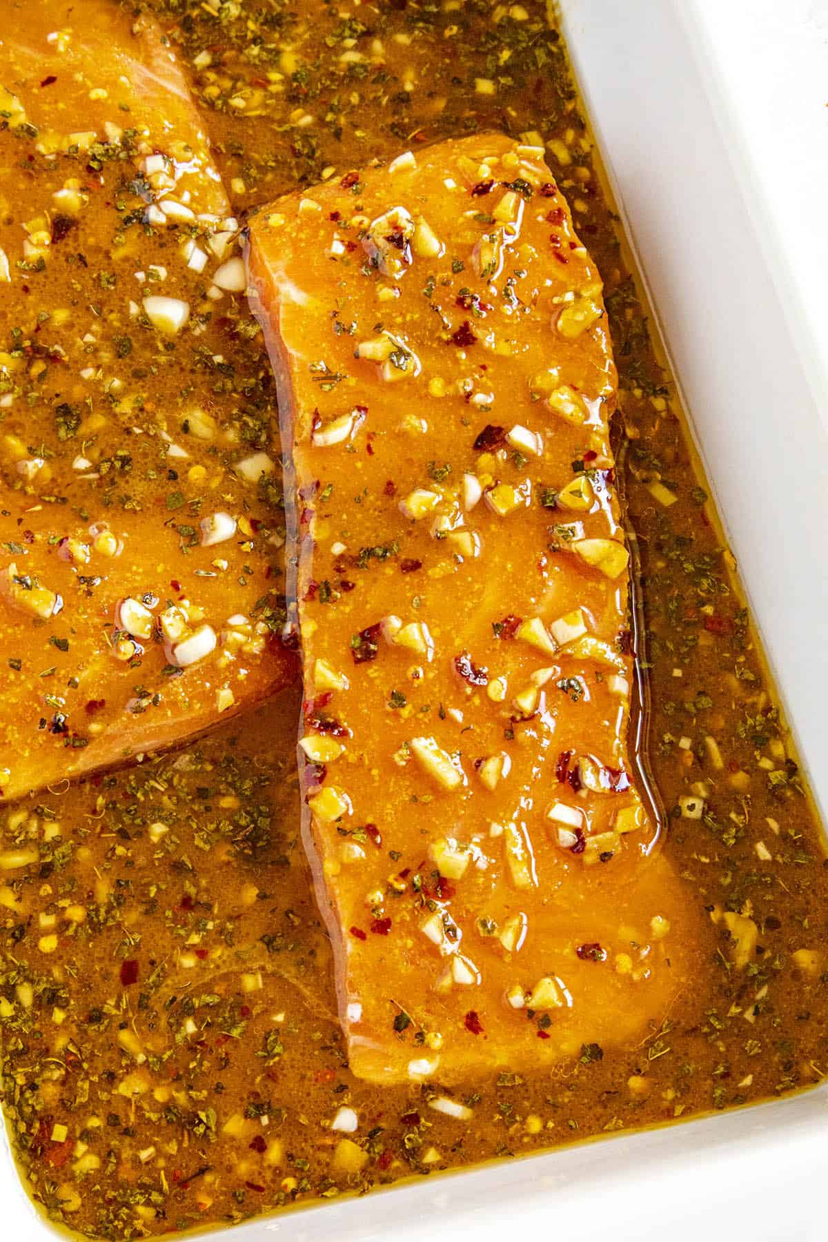 Slices of pink salmon marinating in a bowl of spicy salmon marinade
