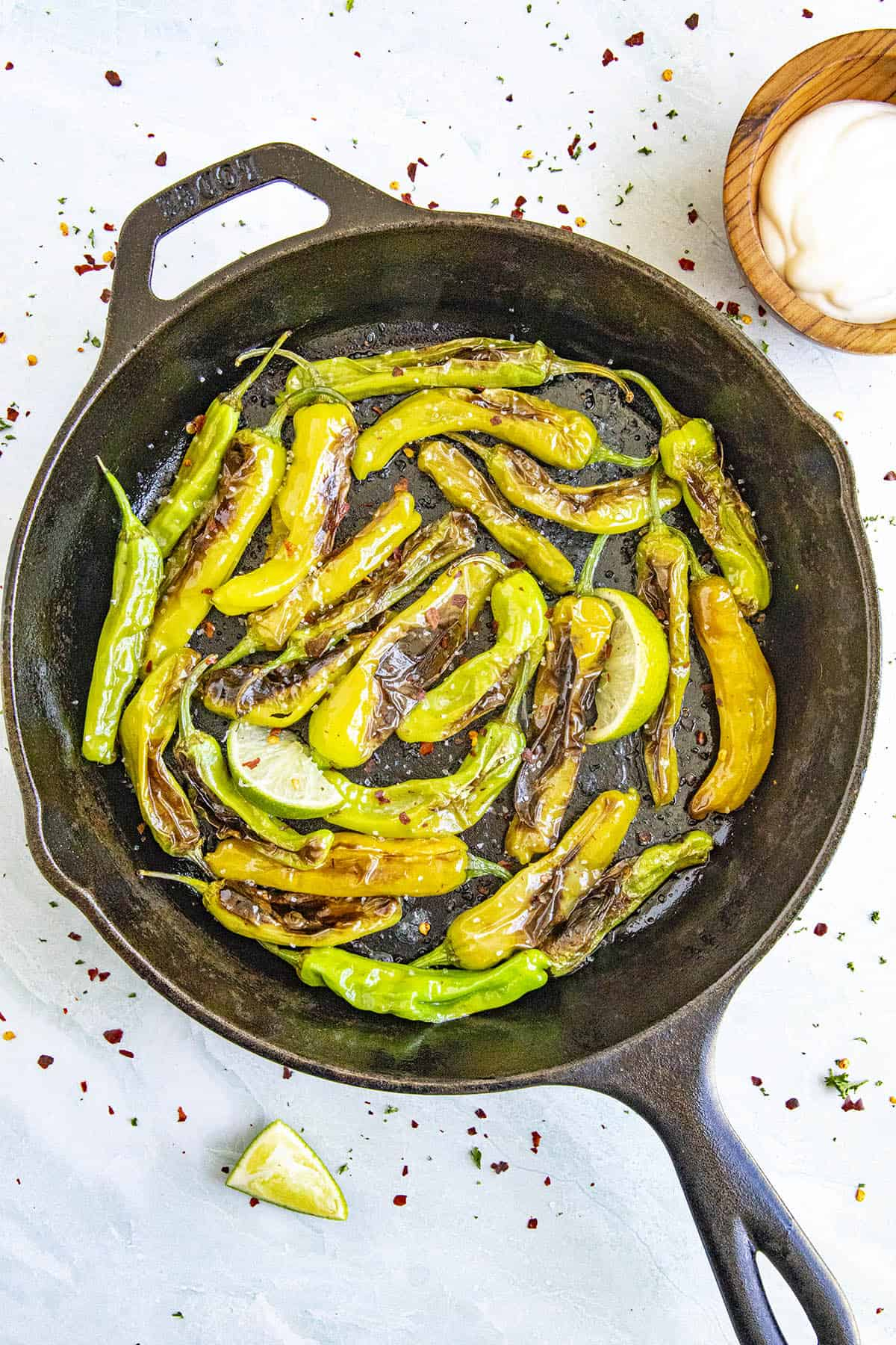 Hot Blistered Shishito Peppers in a pan with salt and lime