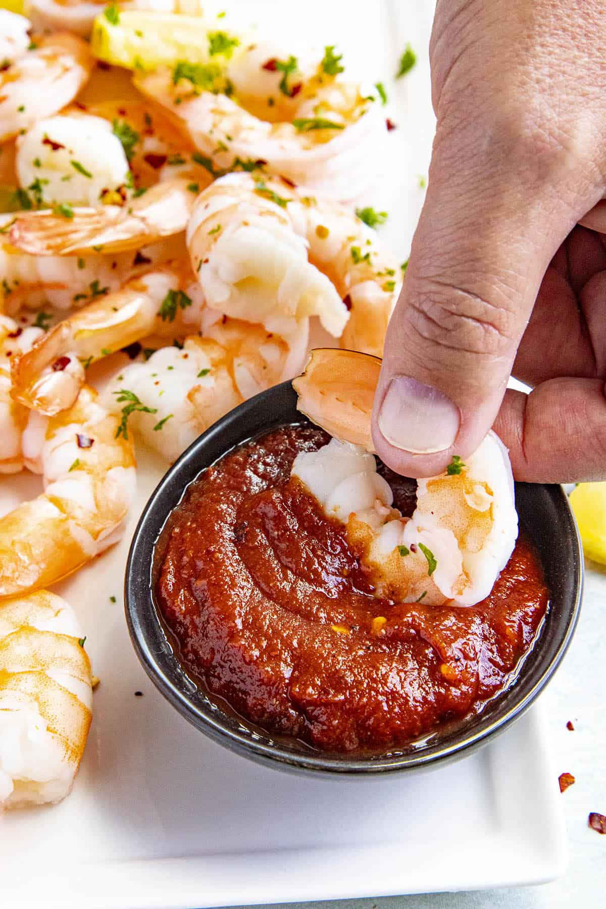Dipping a piece of shrimp into a bowl of homemade chili sauce