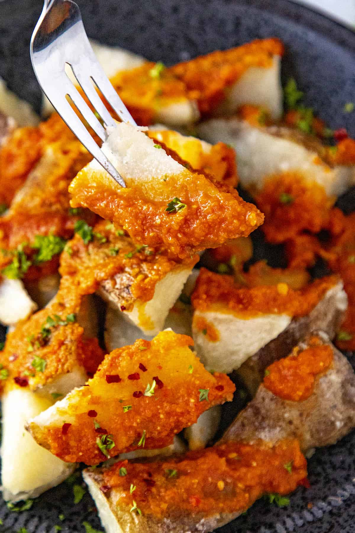 Patatas Bravas on a fork, covered with spicy bravas sauce