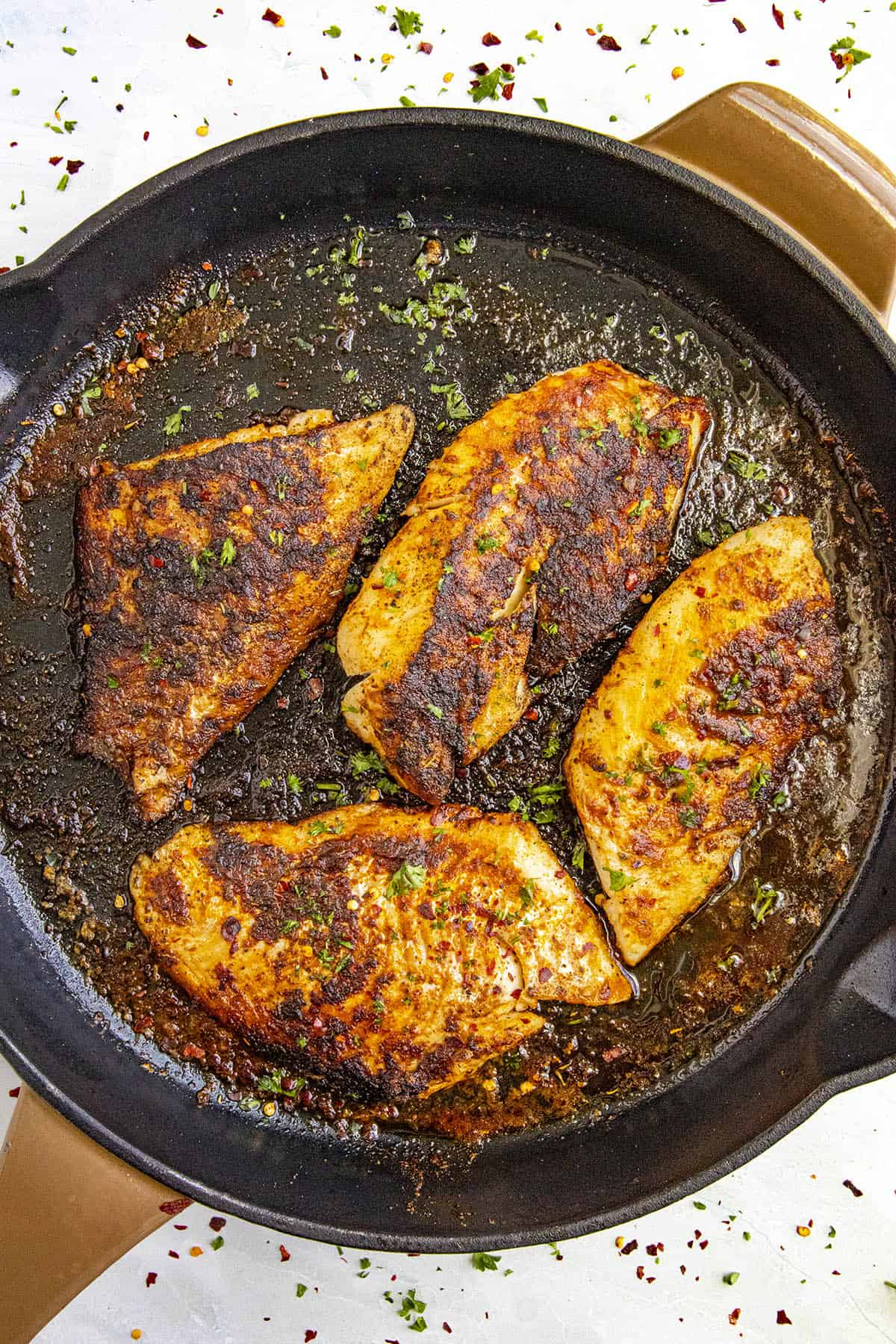 Spicy Blackened Fish in a pan with lots of seasoning