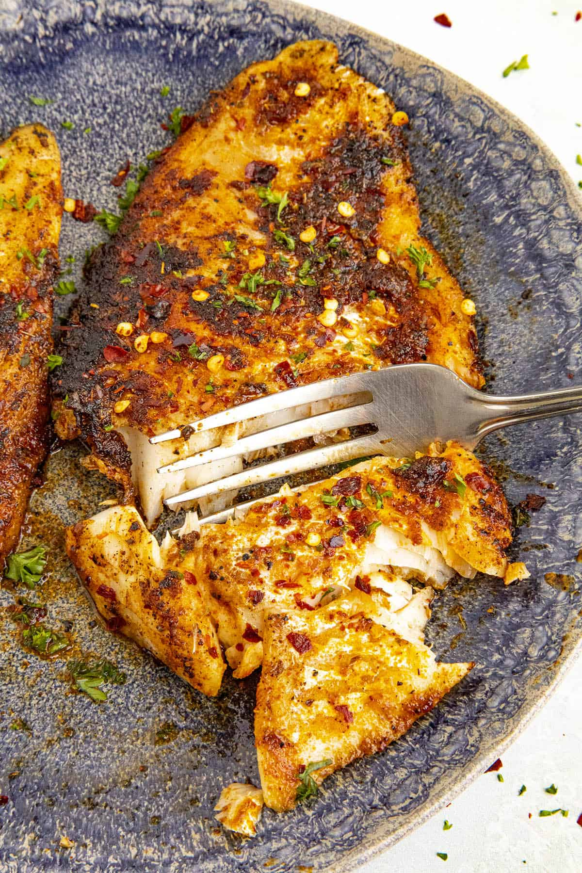 Taking a scoop with a fork of my spicy blackened fish
