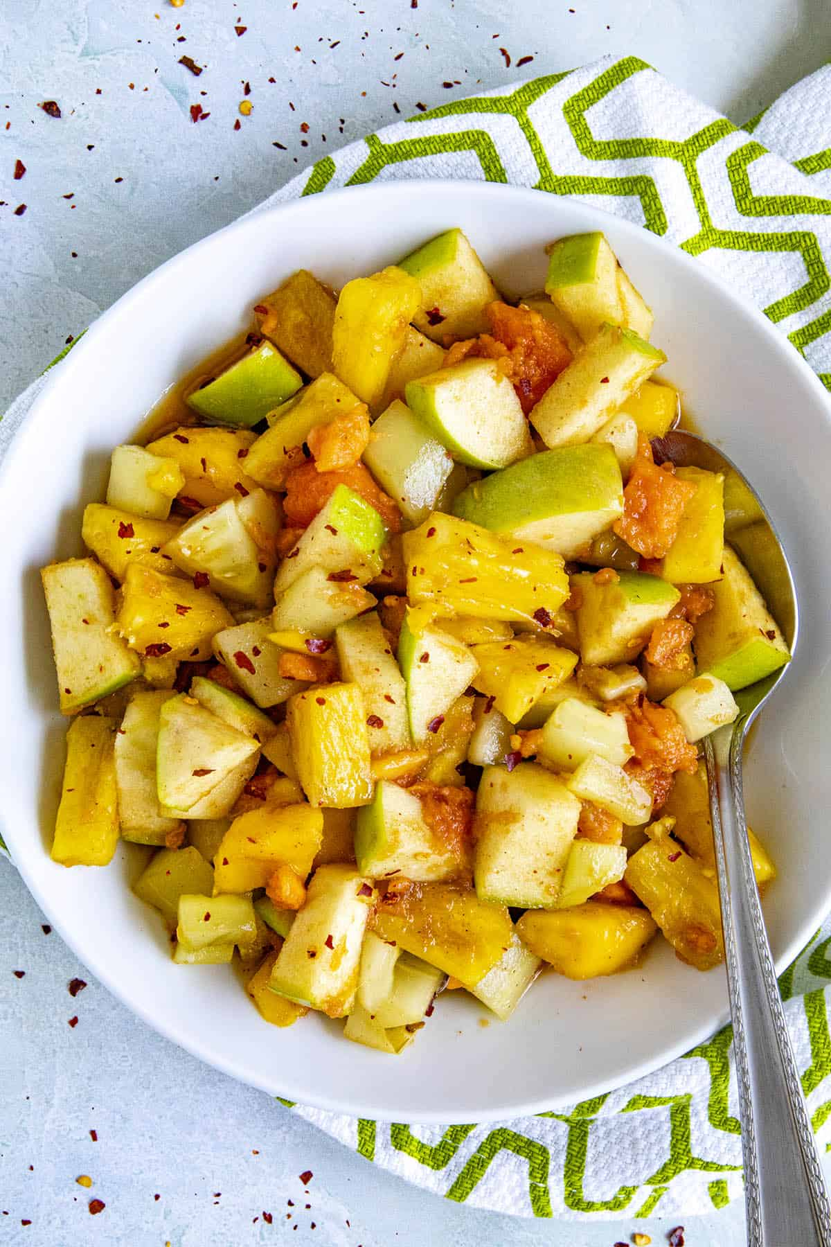 Rujak (Indonesian fruit salad) in a bowl with a spoonful of fruit