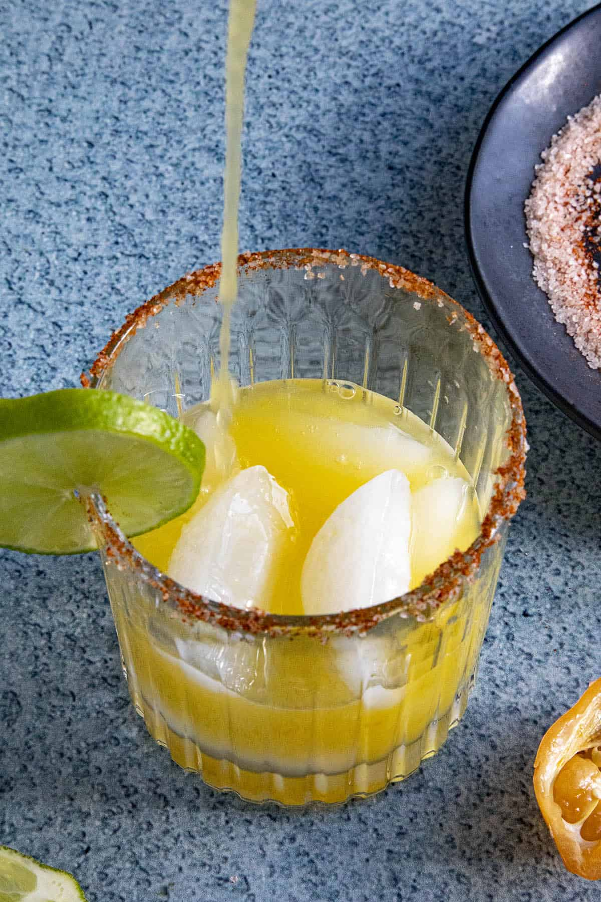 Pouring some Spicy Mango Margarita into a glass with ice