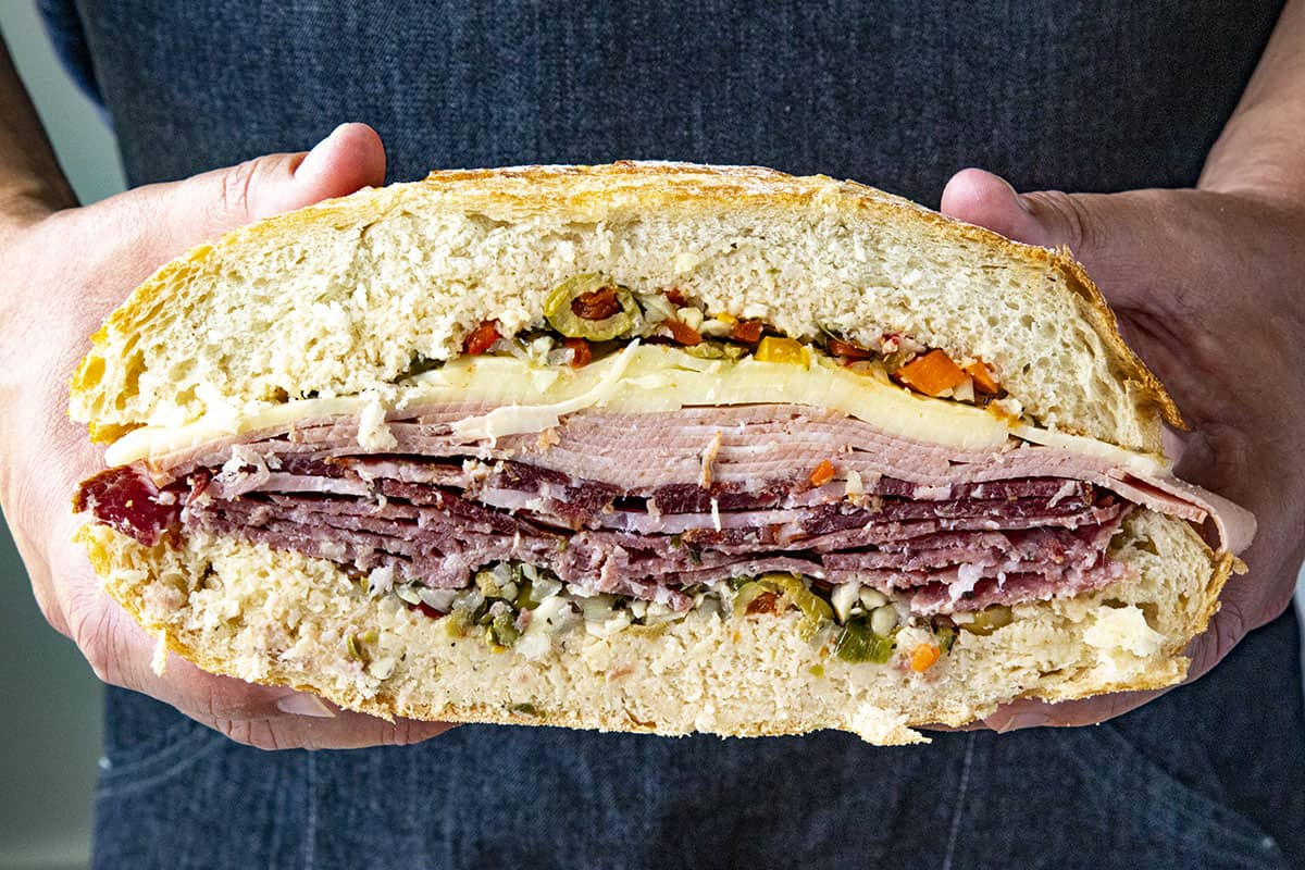A thick and meaty Muffaletta sandwich sliced in half, showing all of the layers of meats and cheese