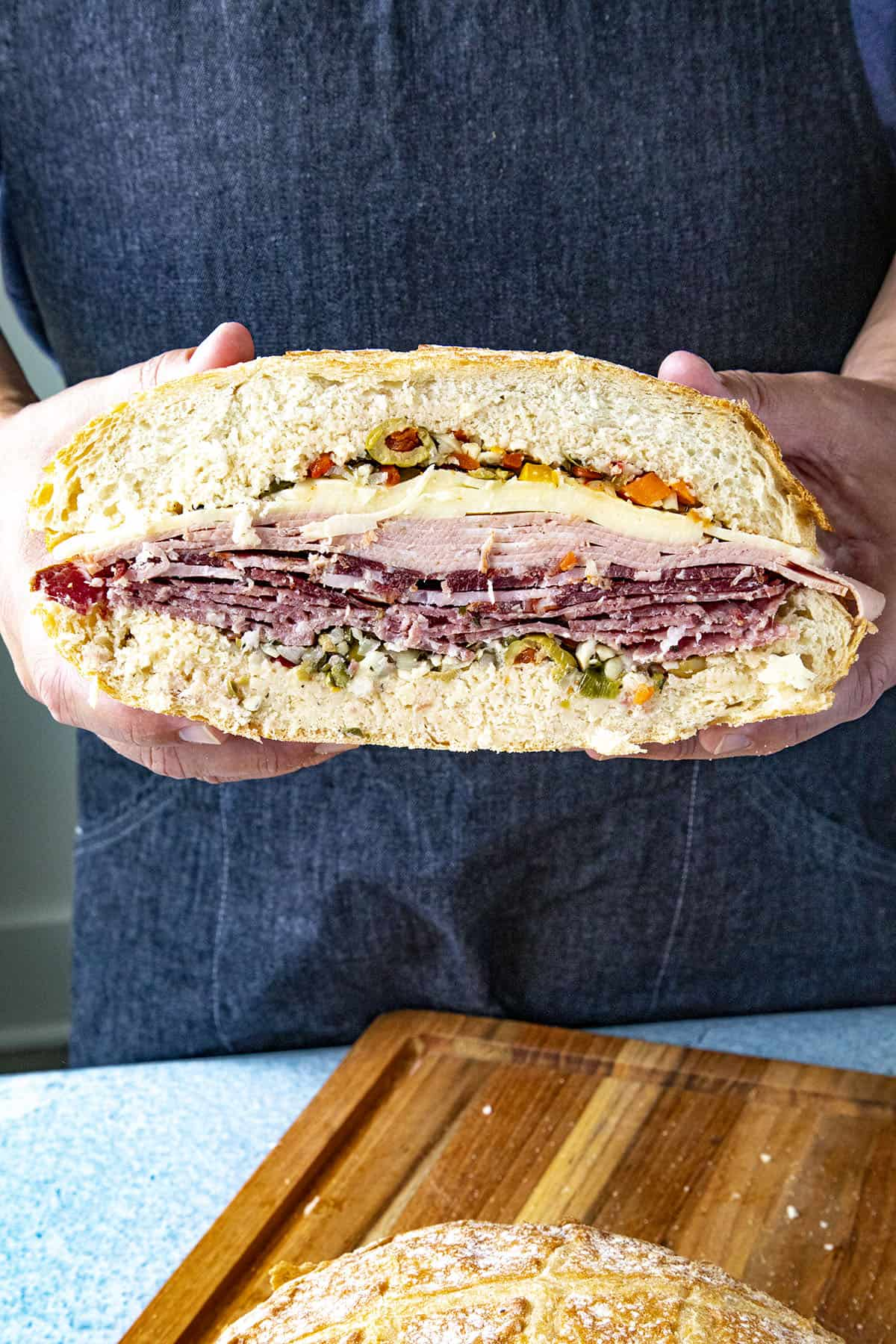 A thick and meaty Muffaletta sandwich sliced in half