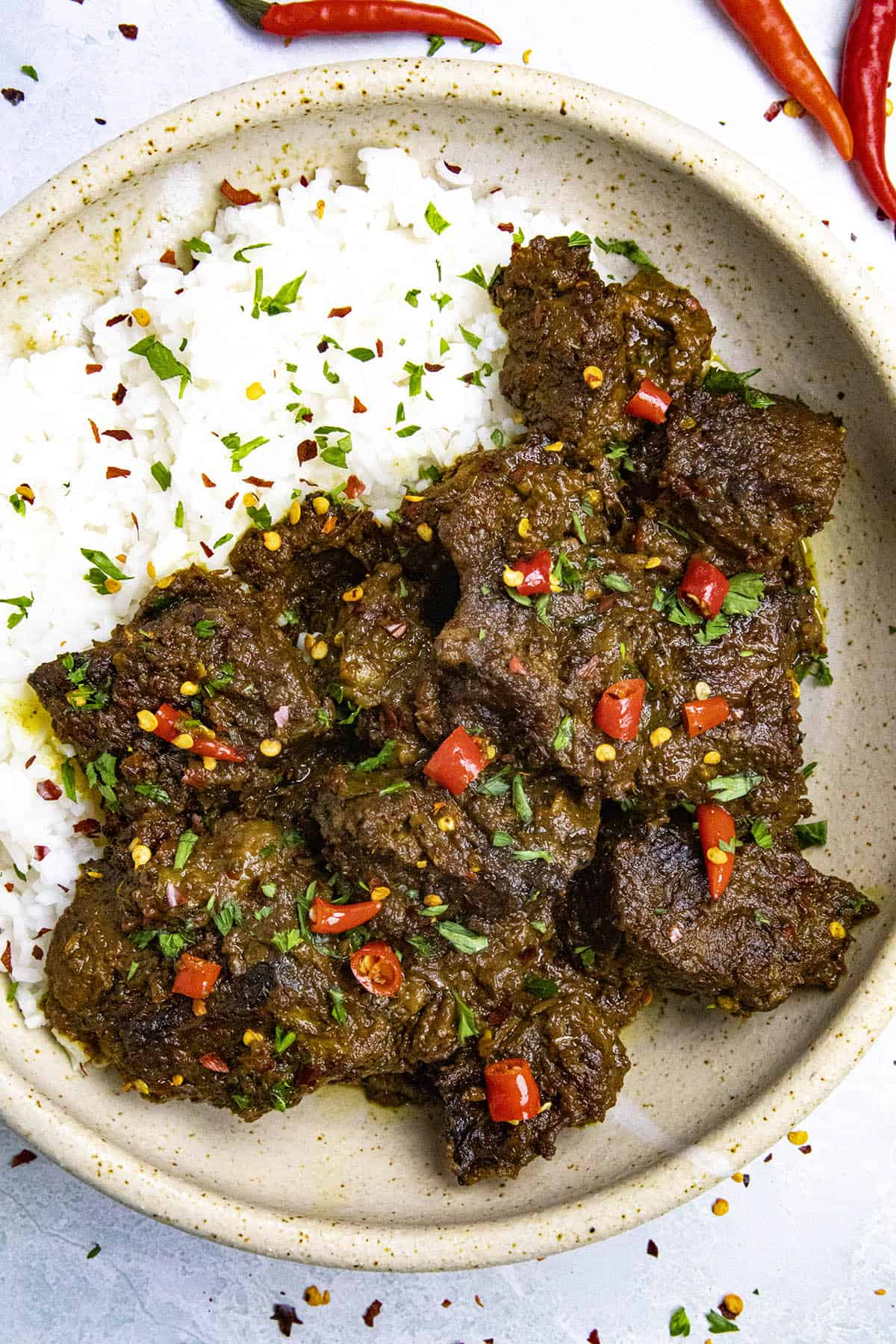 Beef Rendang in a bowl with sliced chili peppers as garnish