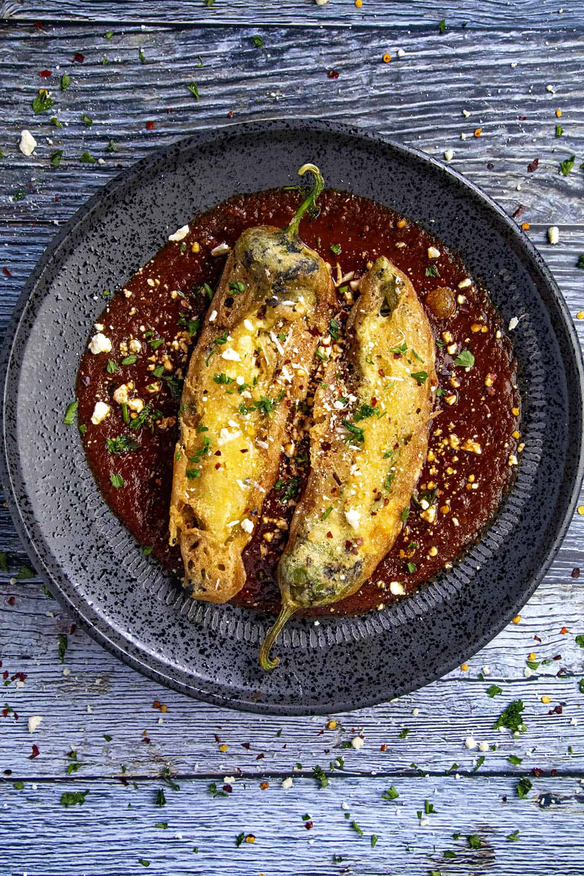 Two Chiles Rellenos on a plate with salsa roja (red sauce)