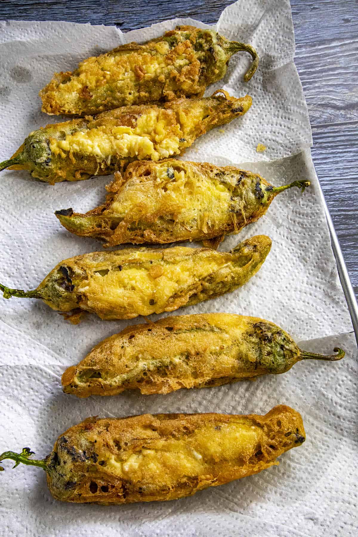 Chiles rellenos just out of the fryer, draining on paper towels
