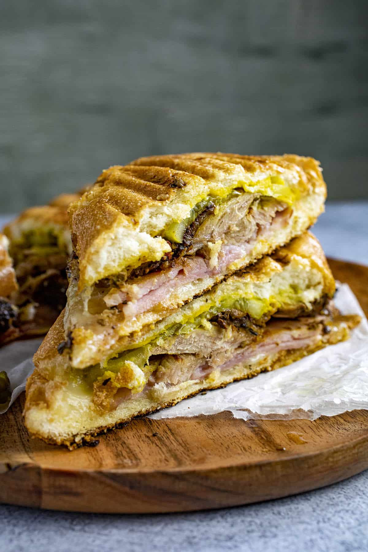 Cuban Sandwiches on a plate with lots of pulled pork, ham, pickles and mustard