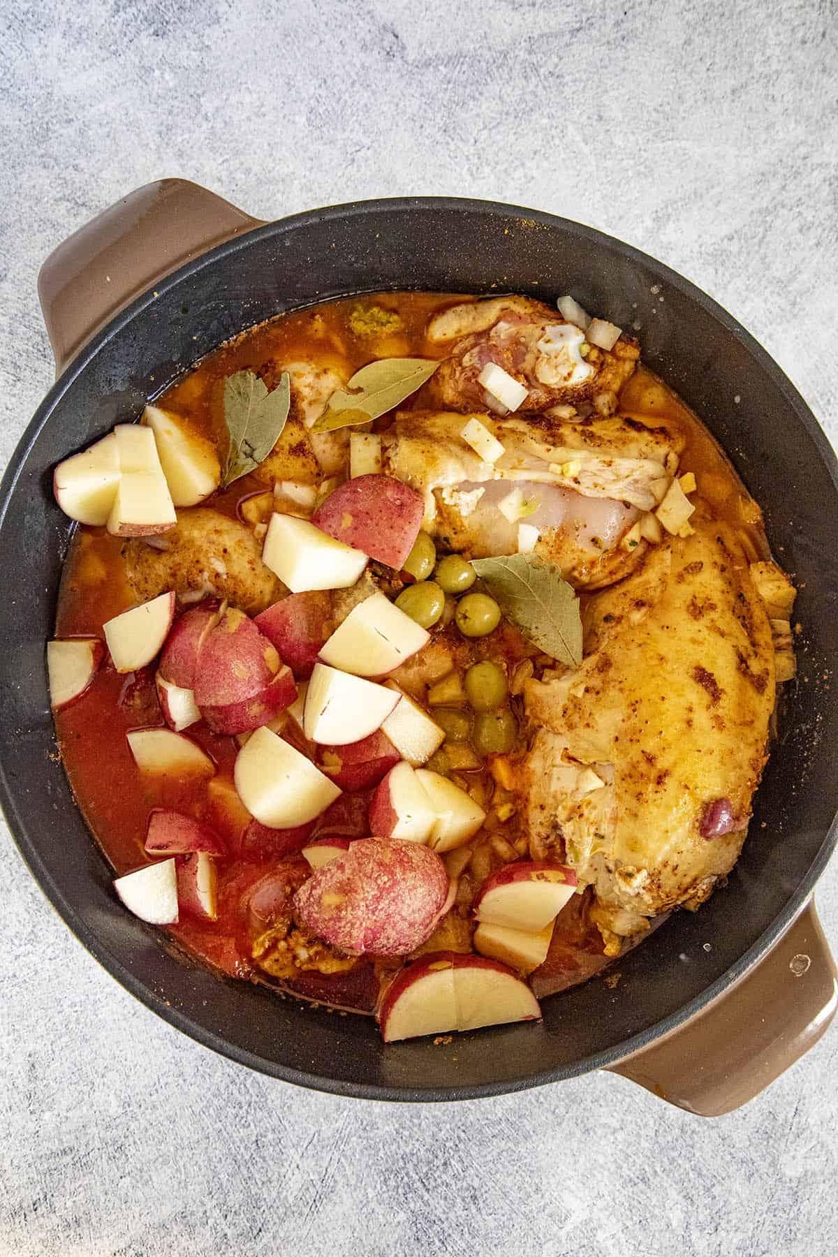 Simmering the pollo guisado in a pot