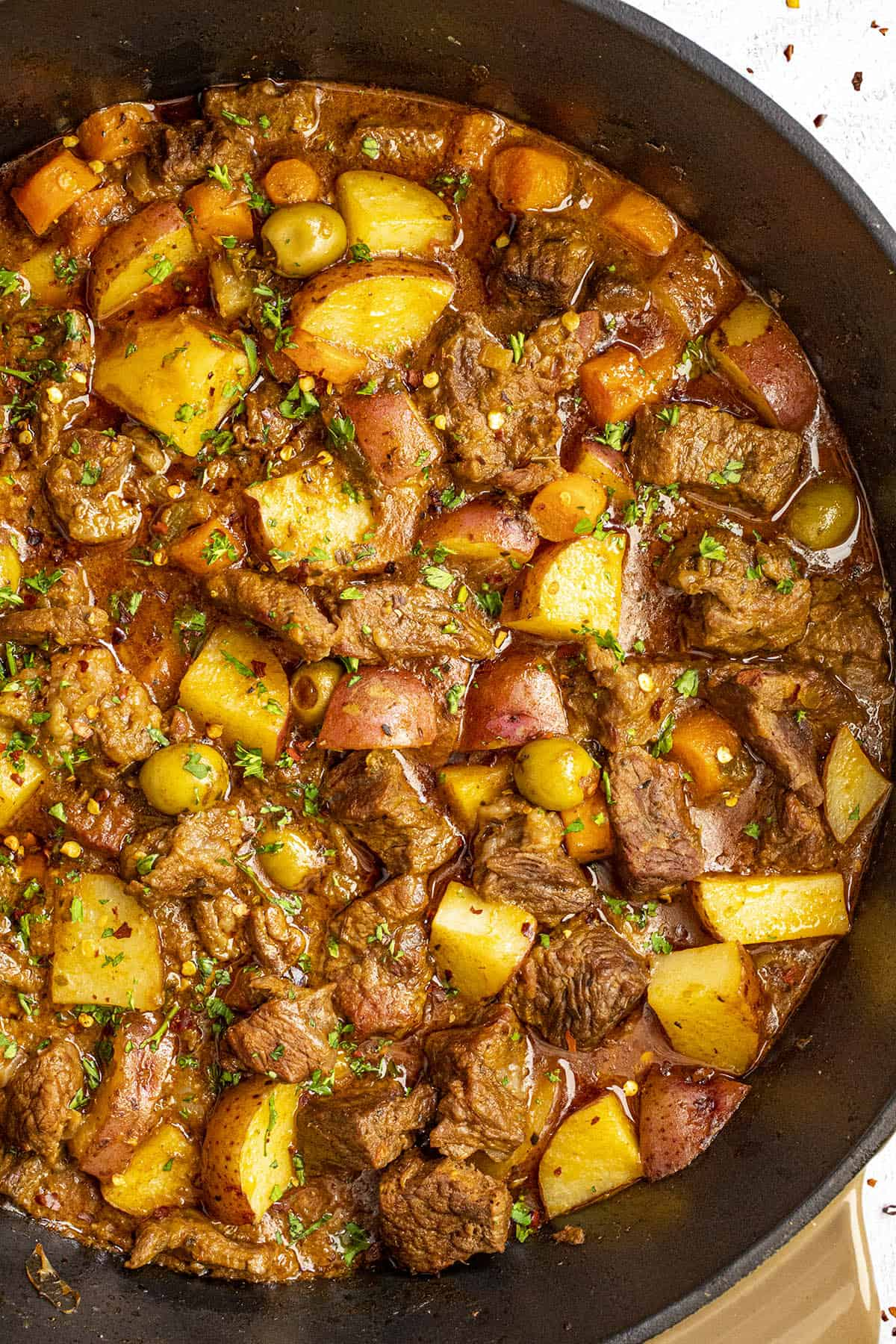 Carne guisada (beef stew) in a pot with garnish
