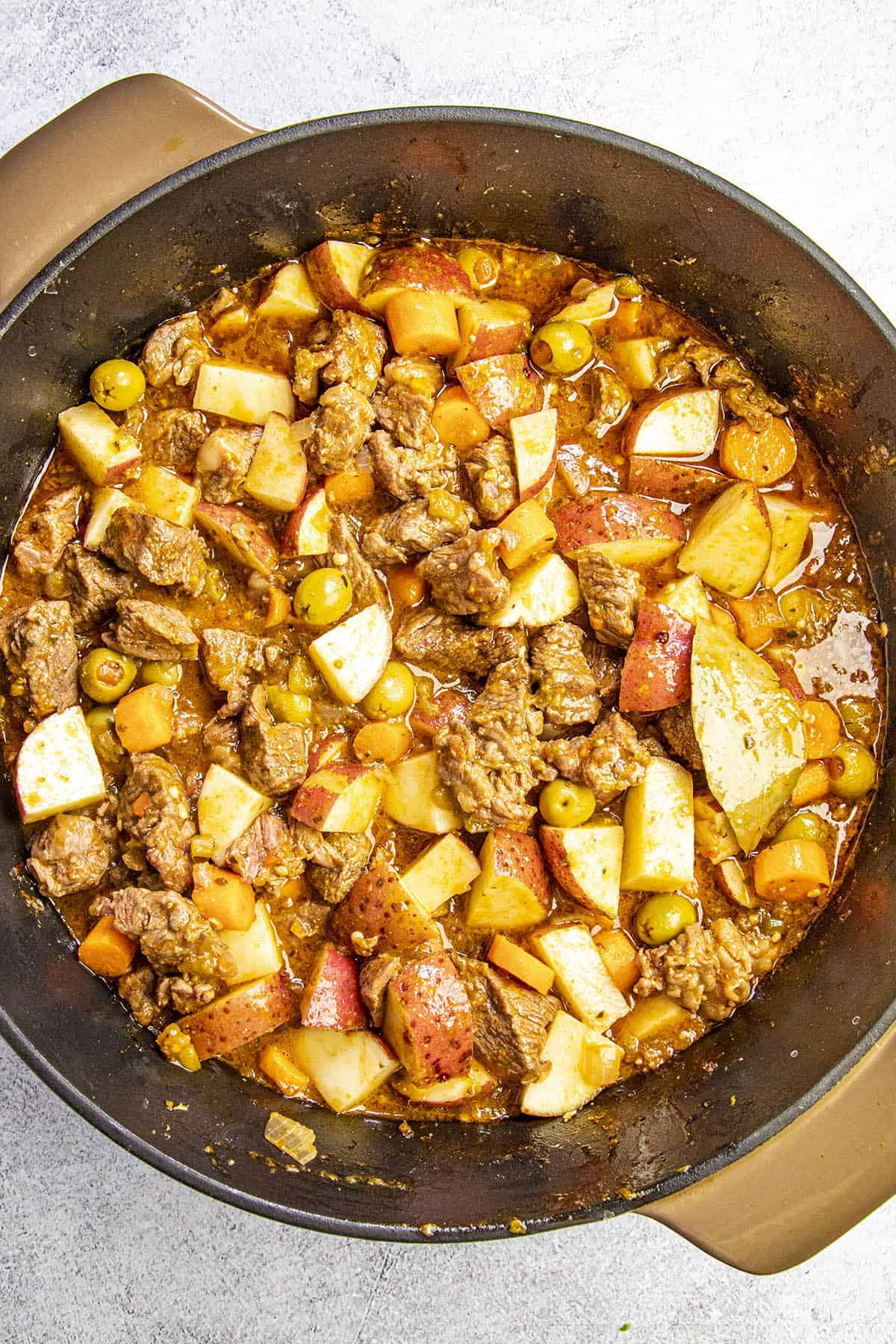 Cooking down the beef and vegetables in a pot to make carne guisada (beef stew)