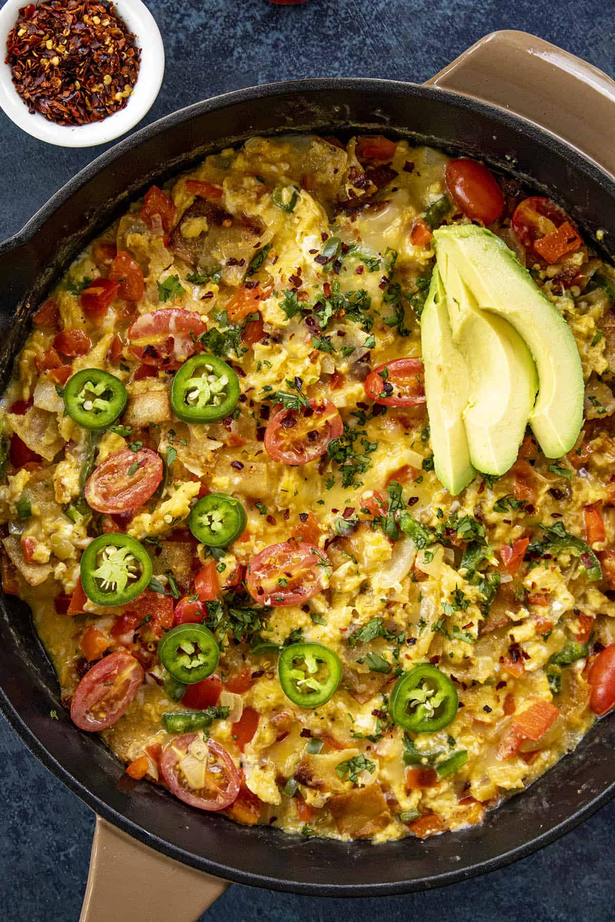 A big pan of Migas (Easy Mexican Scrambled Eggs with Crispy Tortillas), with avocado slices, sliced peppers, tomatoes and more