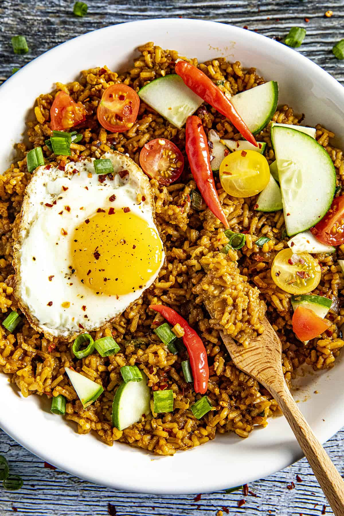 Taking a forkful of Indonesian Fried Rice (Nasi Goreng) from a bowl