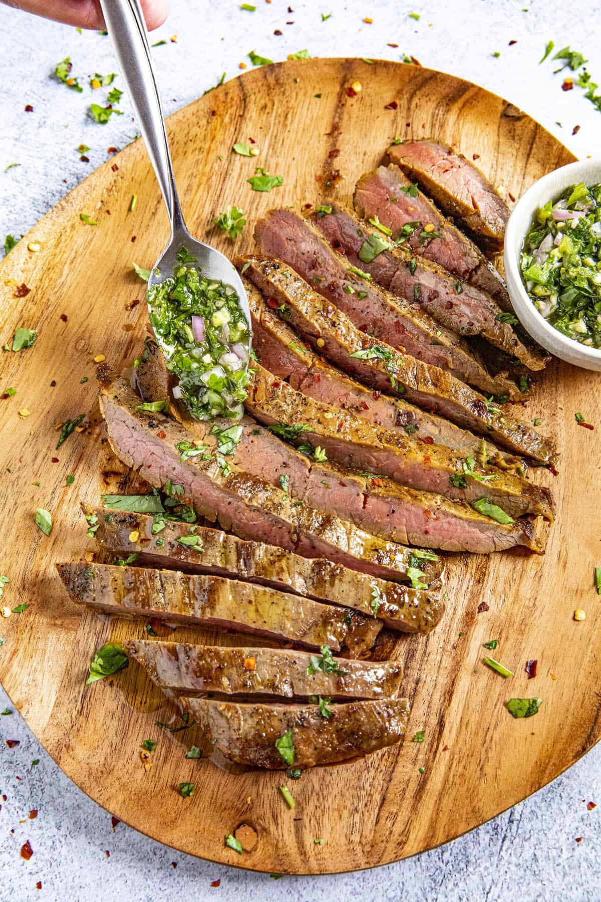 Mike spooning Chimichurri onto a sliced flank steak