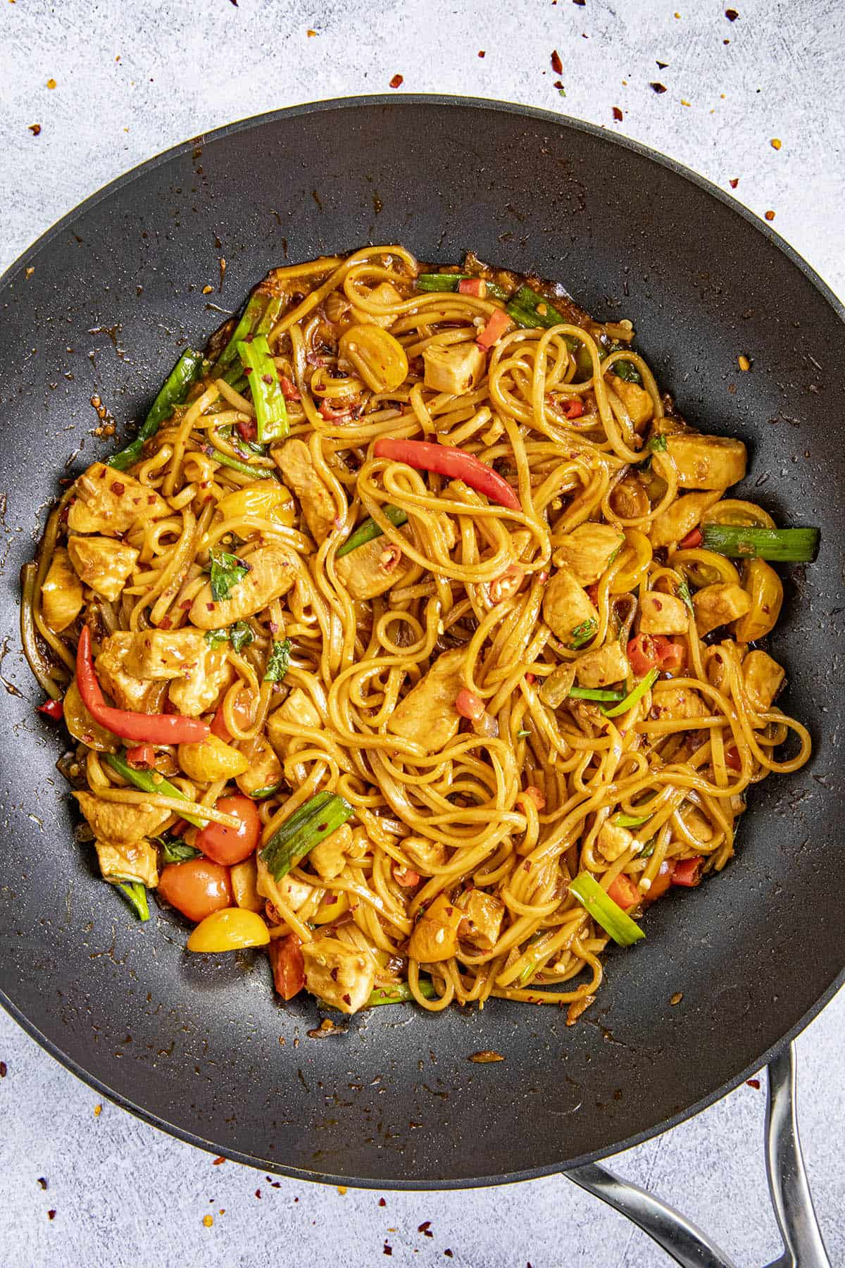 Spicy Drunken Noodles in a pan with chili flakes and green onion