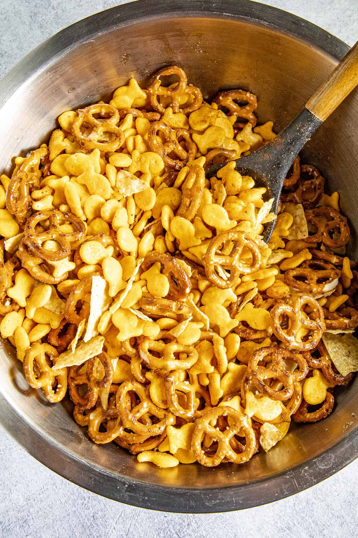 Mixing up my Homemade Spicy Snack Mix in a bowl with seasonings