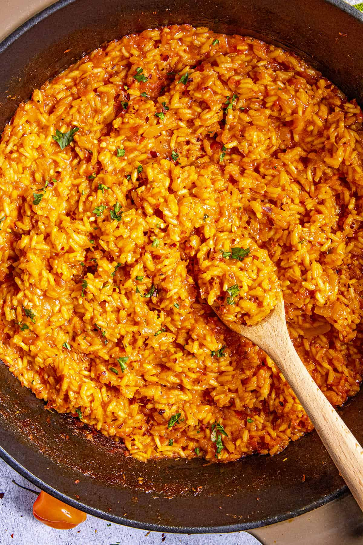 Jollof Rice in a pot with a spoon, ready to serve
