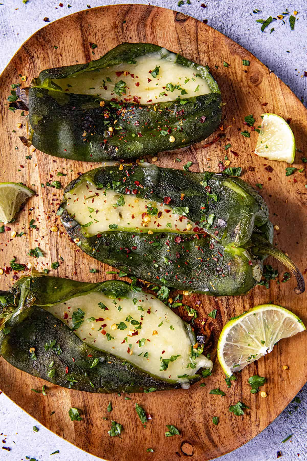 Three Poblano peppers stuffed with cheese on a plate