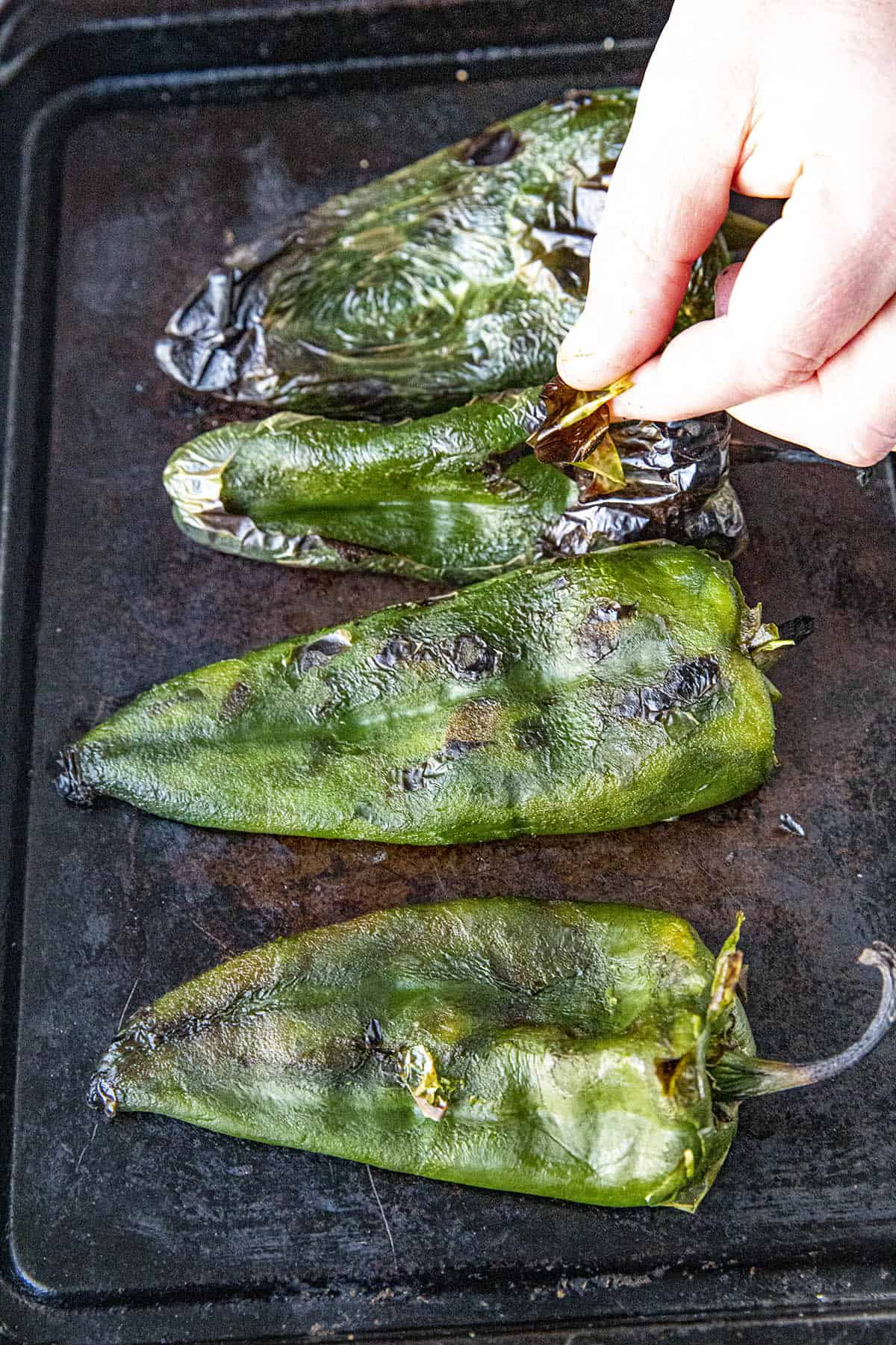 Peeling the grilled poblano peppers