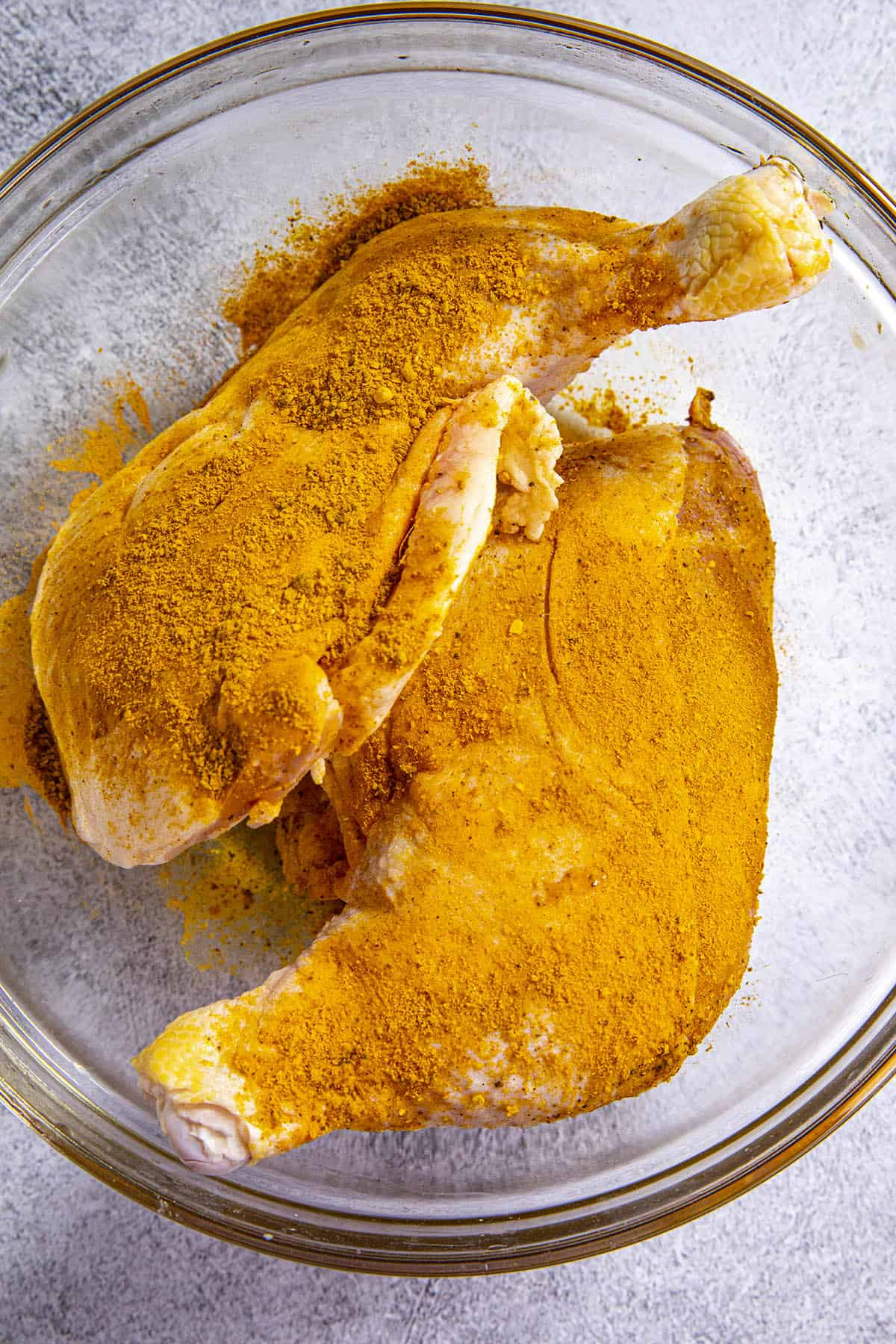 Seasoning 2 large pieces of chicken with homemade Jamaican Curry powder
