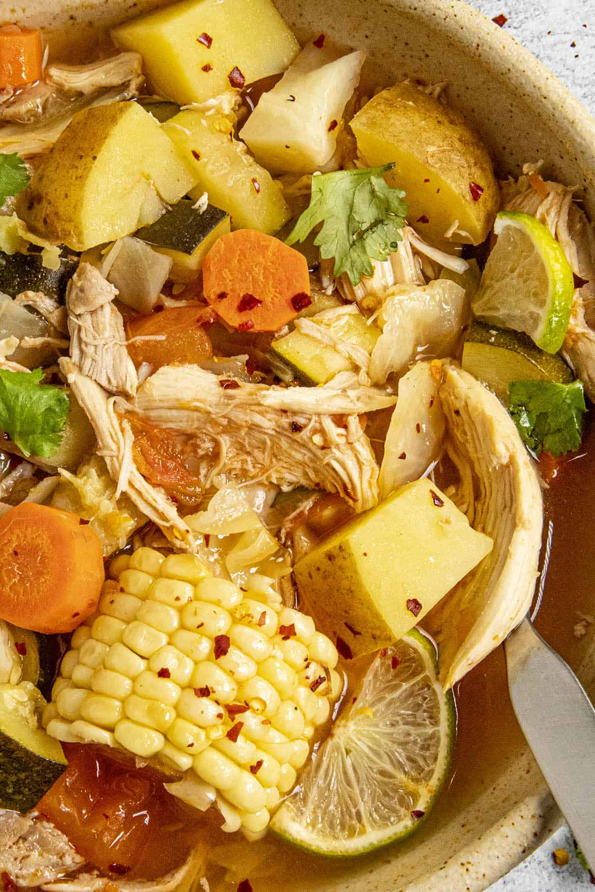 Chunky Caldo de Pollo in a bowl with lots of chicken and vegetables