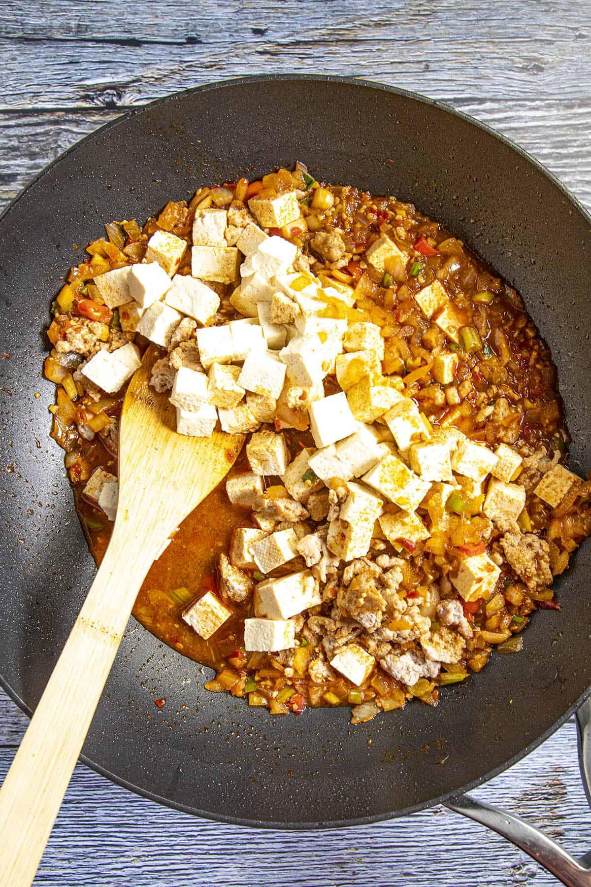 Stirring the tofu into my pan of Mapo Tofu