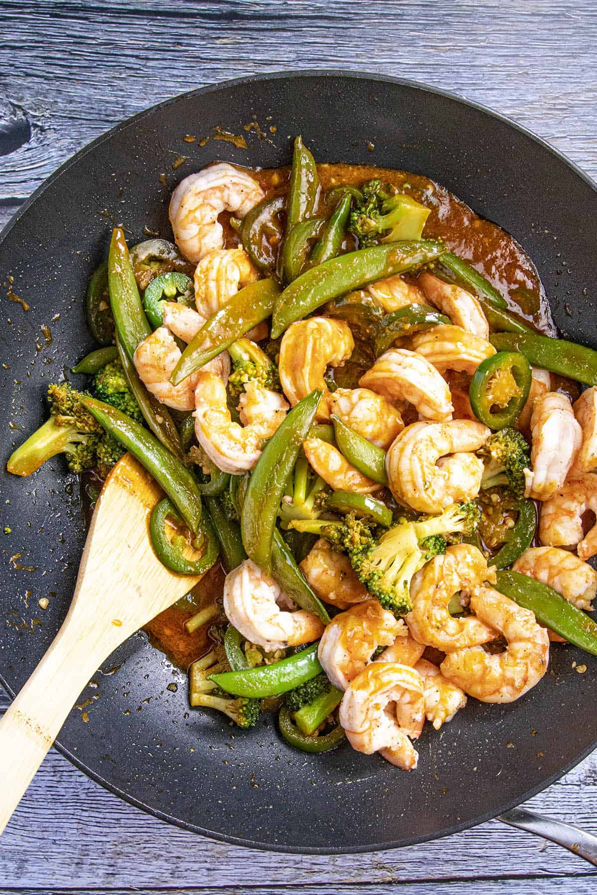Mixing in the spicy shrimp stir fry ingredients together in a wok