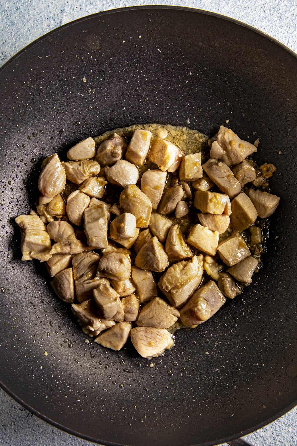 Cooking chicken in a wok to make Bourbon Chicken