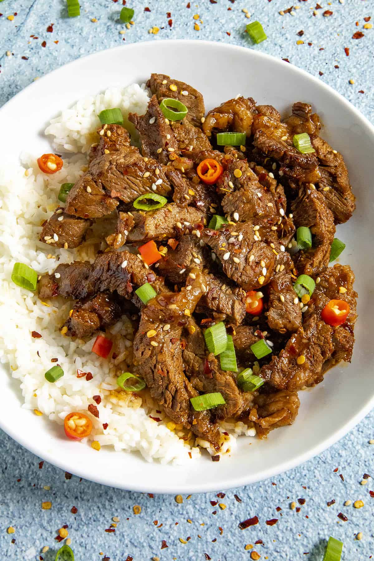 Bulgogi in a bowl, garnished with sesame seeds, green onion and peppers