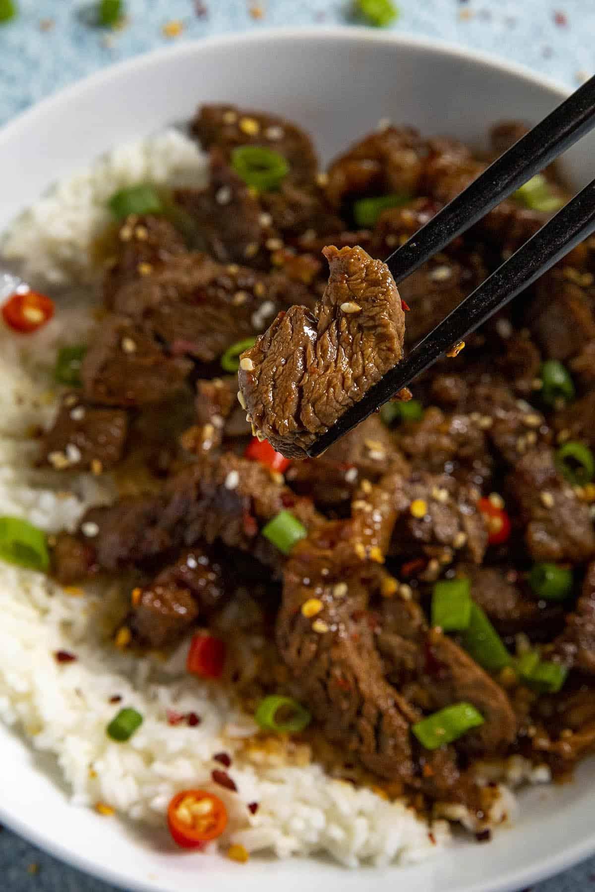 Chopsticks grabbing a slice of bulgogi from a bowl