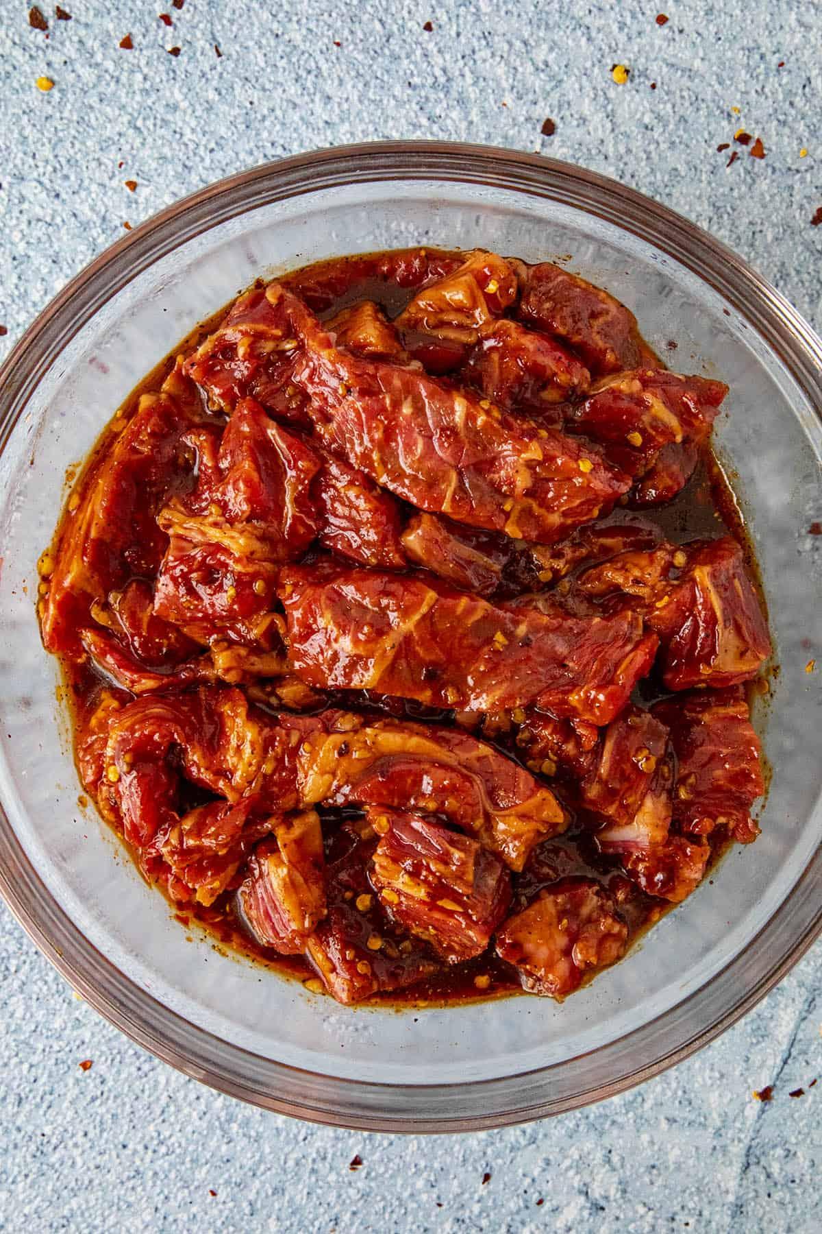 Sliced ribeye steak marinating in a bowl with bulgogi sauce