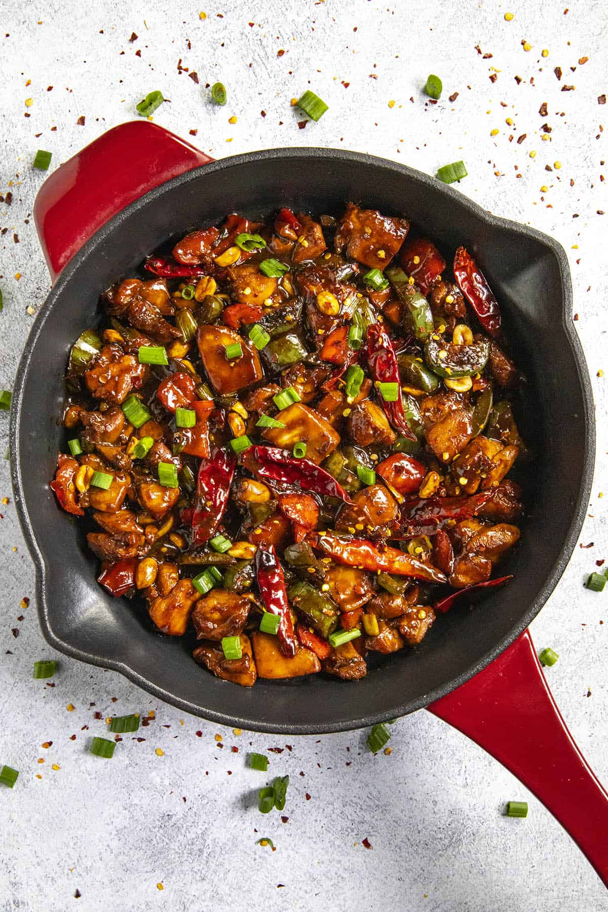 Kung Pao Chicken in a pan with lots of chopped green onion