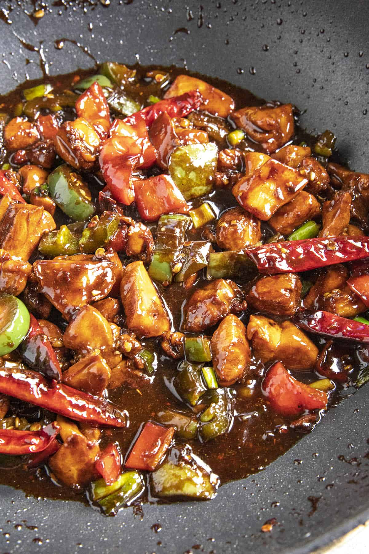 Simmering the Kung Pao Chicken in a pan with sauce
