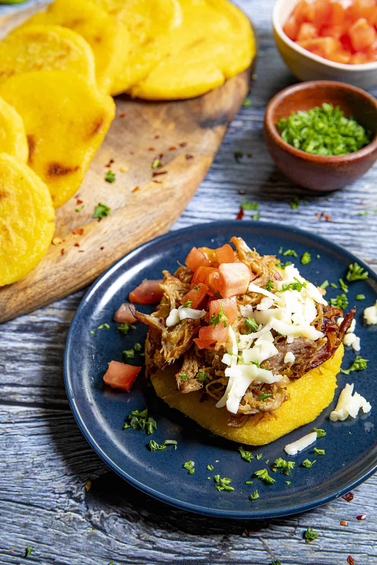 An arepa topped with pulled pork, shredded cheese and diced tomato with an extra stack of arepas
