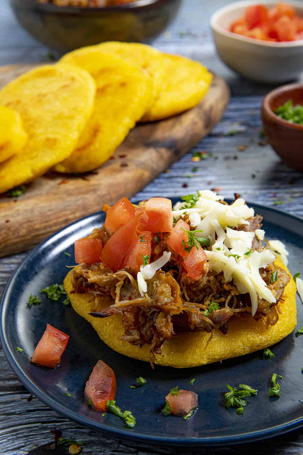 An arepa topped with pulled pork, shredded cheese and tomatoes
