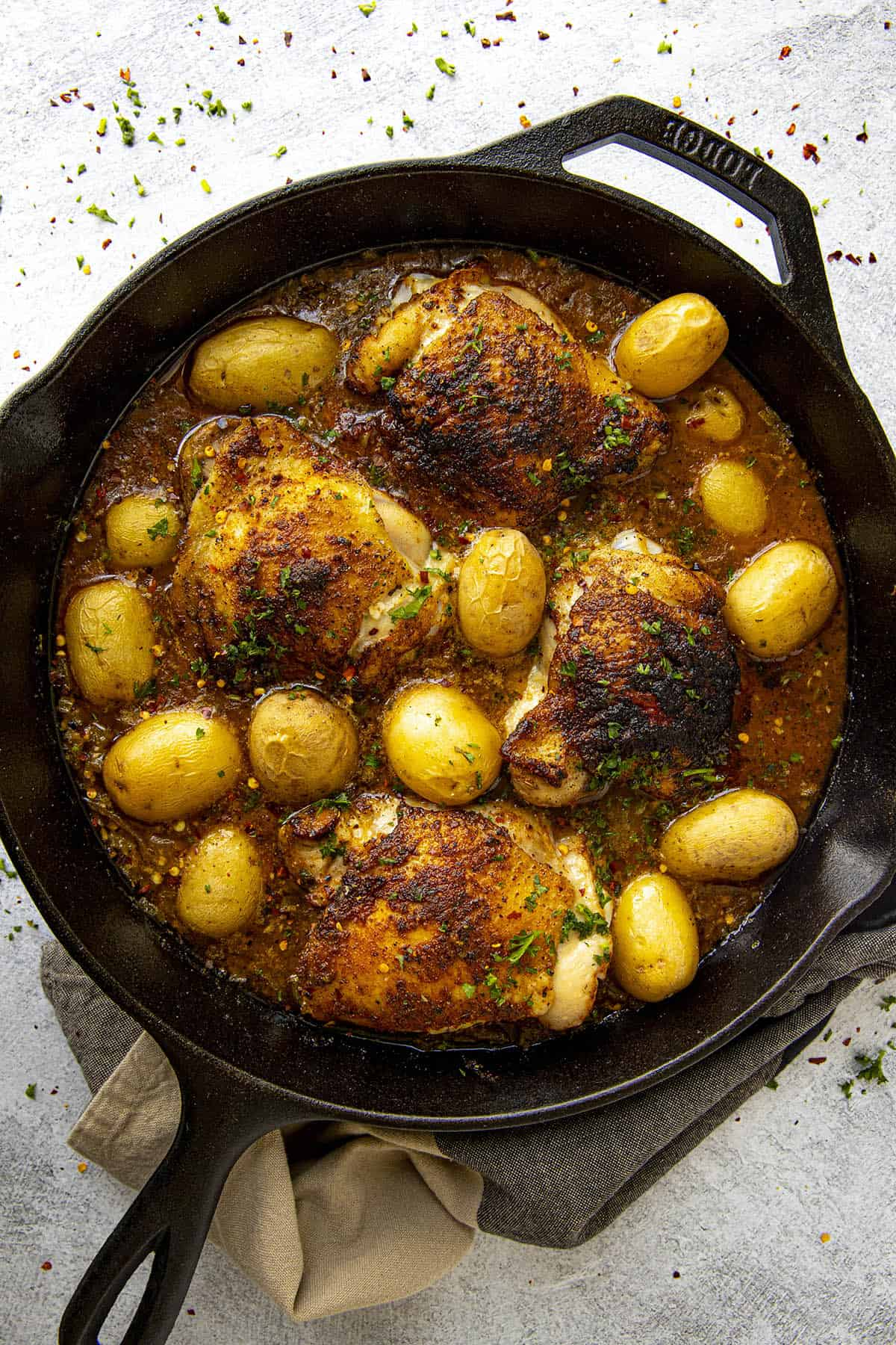 Baked Chicken Thighs in a hot pan with potatoes and lots of Cajun seasonings